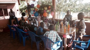 A photo of some of the children at Barb's Home of Angels getting ready for their Christmas dinner! In the middle of the table is a tree they found, which they placed in a pot, and decorated with balloons